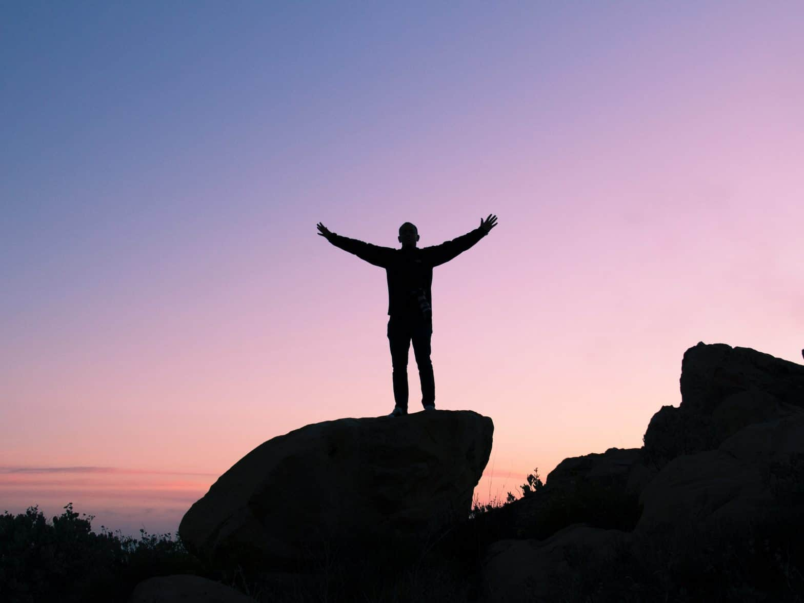 A man on top of a mountain, celebrating successfully achieving his goal. How to set achievable goals.