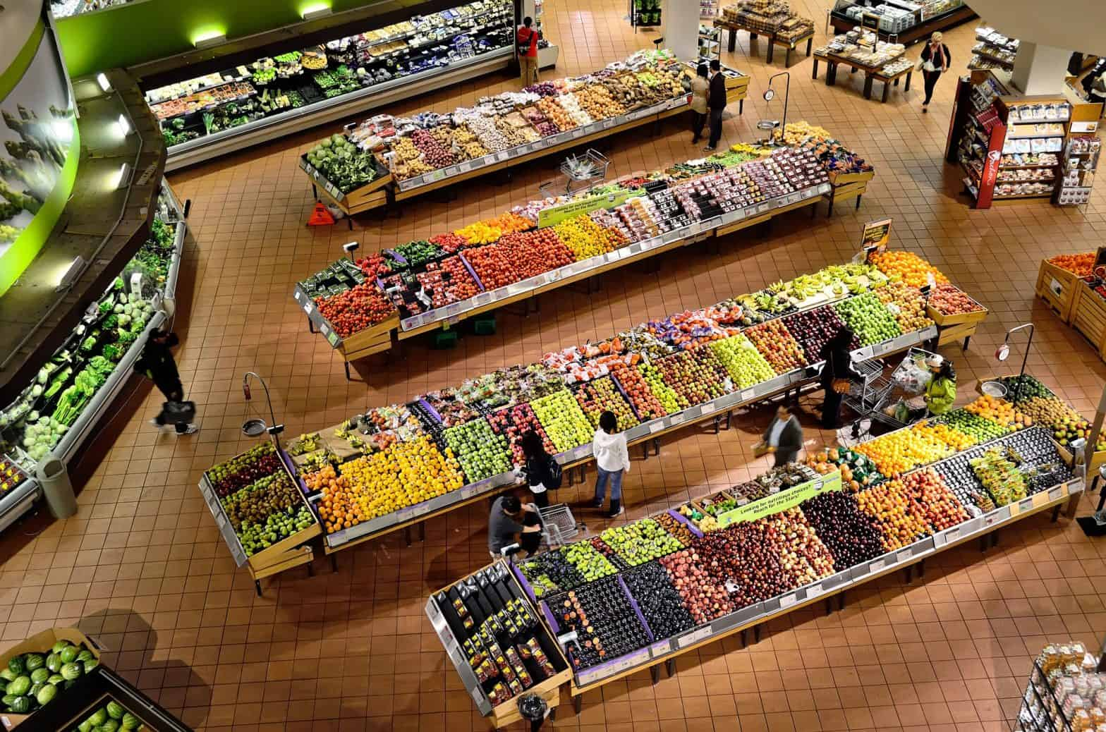 A grocery store with an organized produce section and layout of goods.