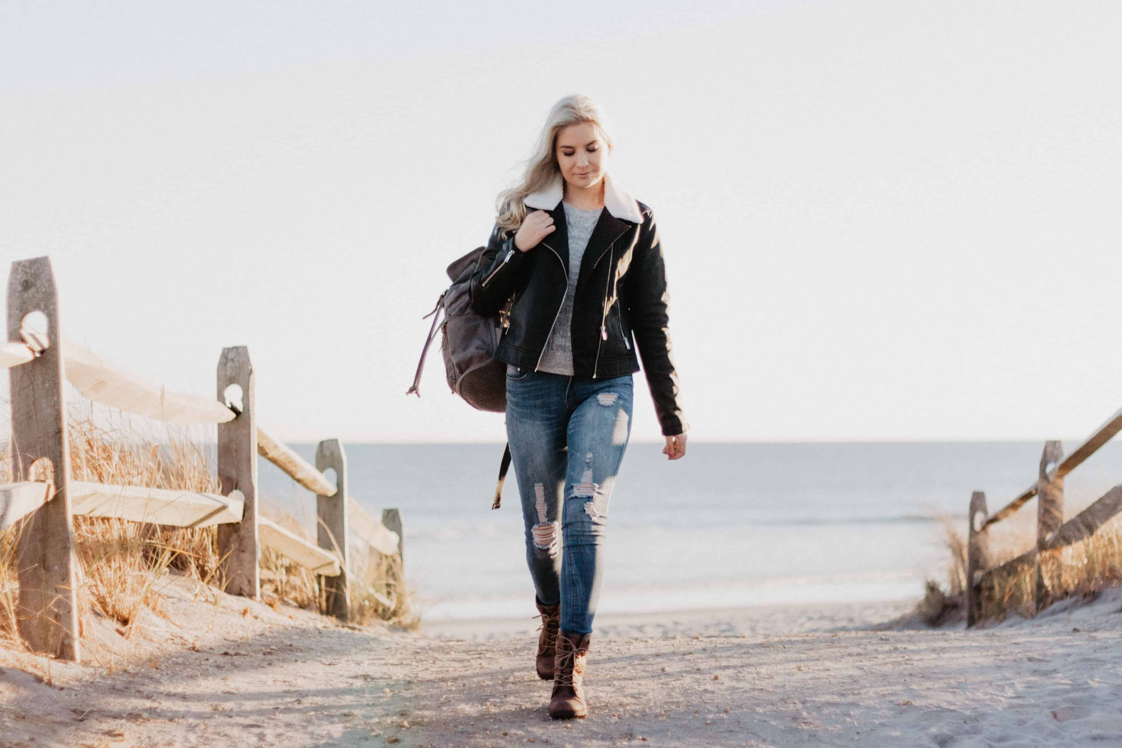 20 benefits of walking, a woman walking by the beach.