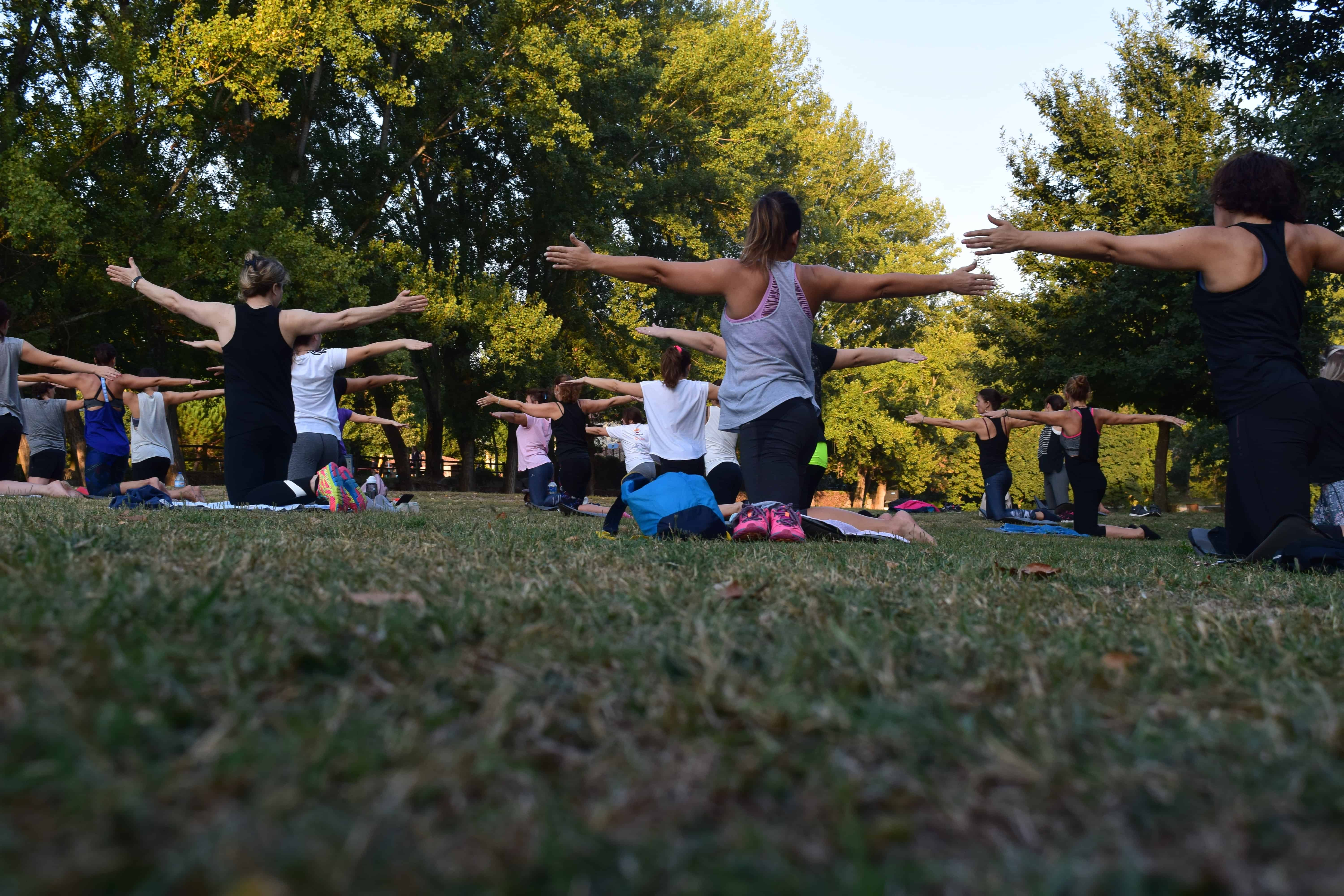 A group of individuals reaping the benefits of practicing yoga in the park.