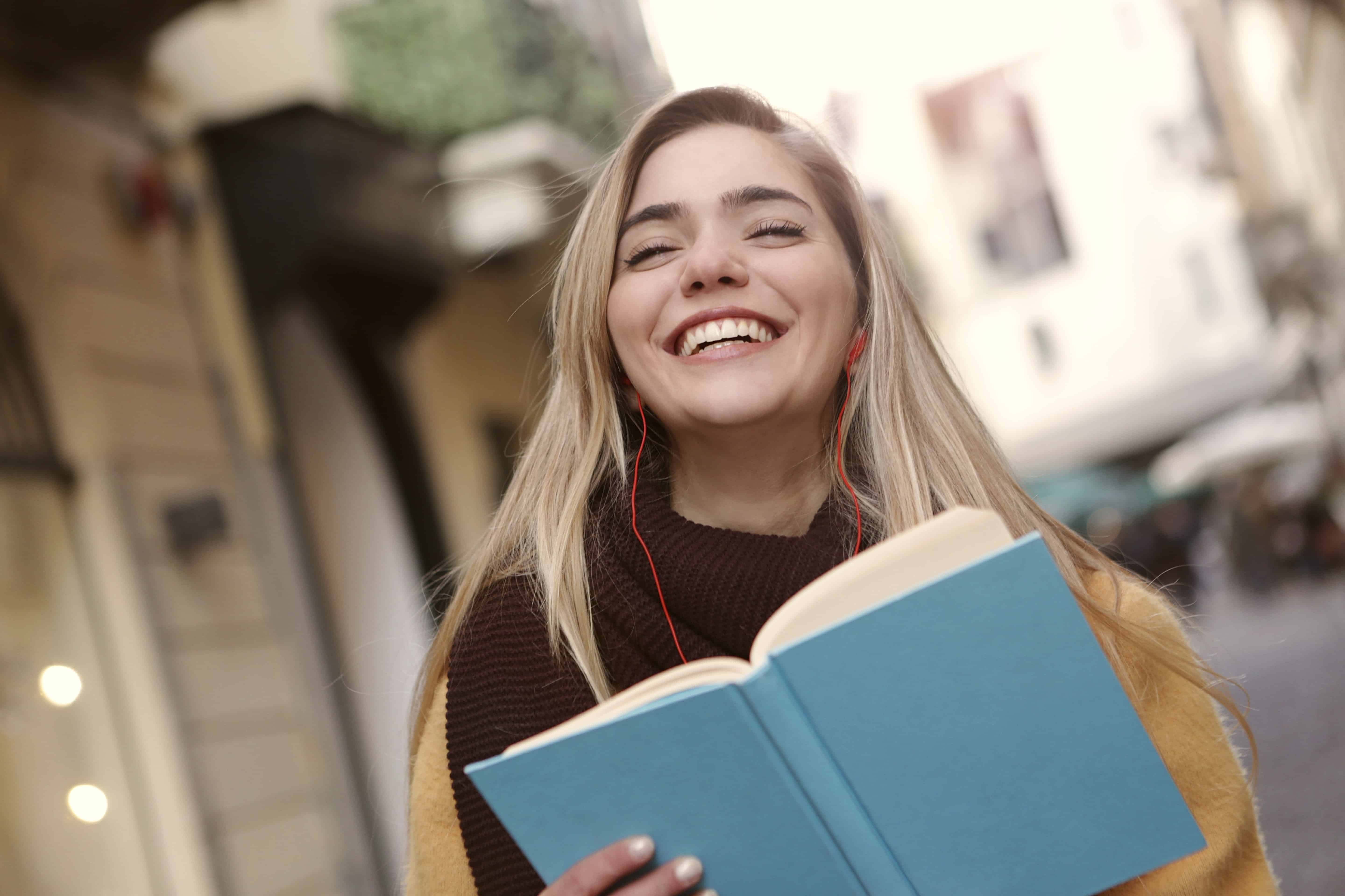 A woman practicing good daily habits by reading and being outside.