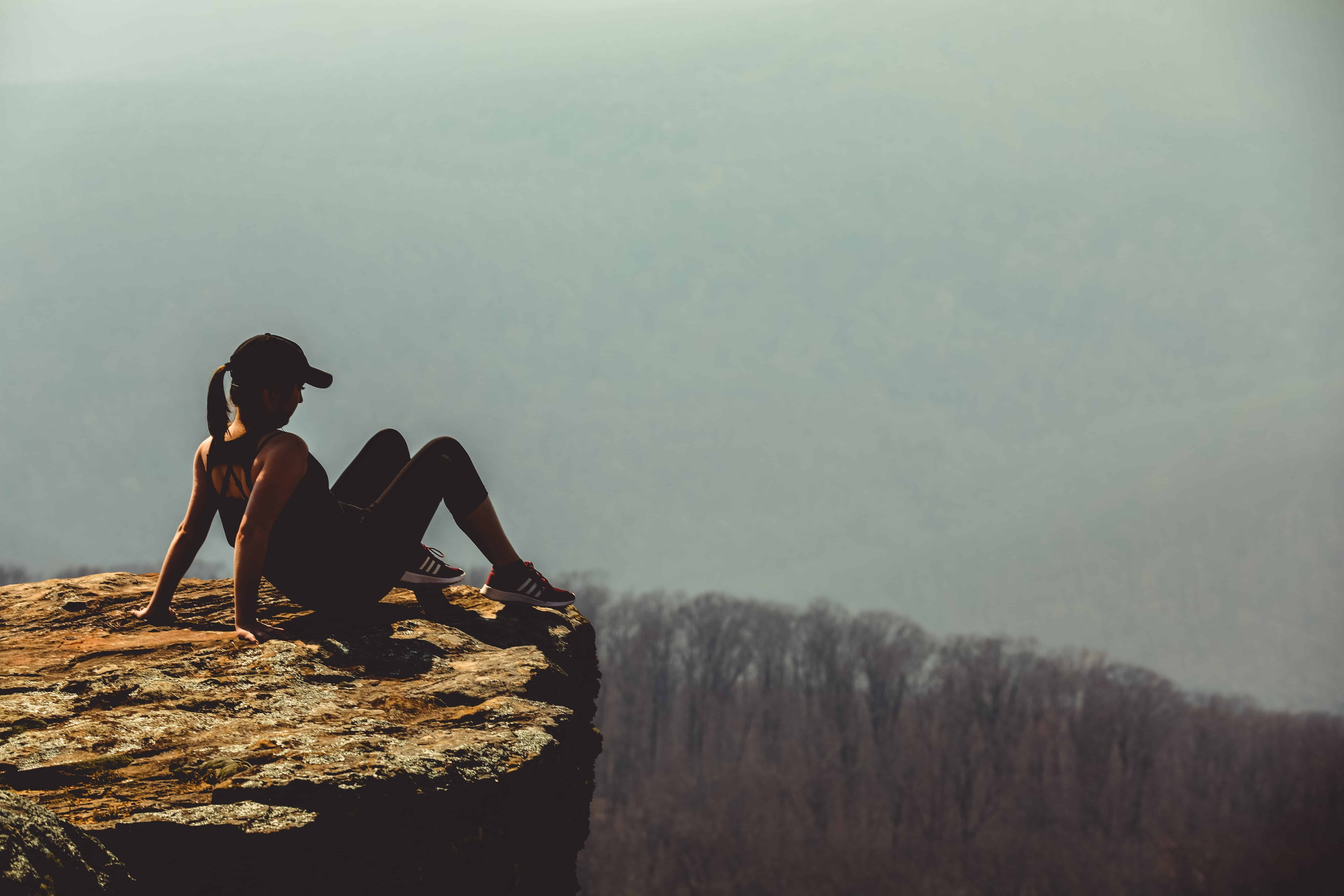 A woman siting on the edge of a cliff taking a risk.