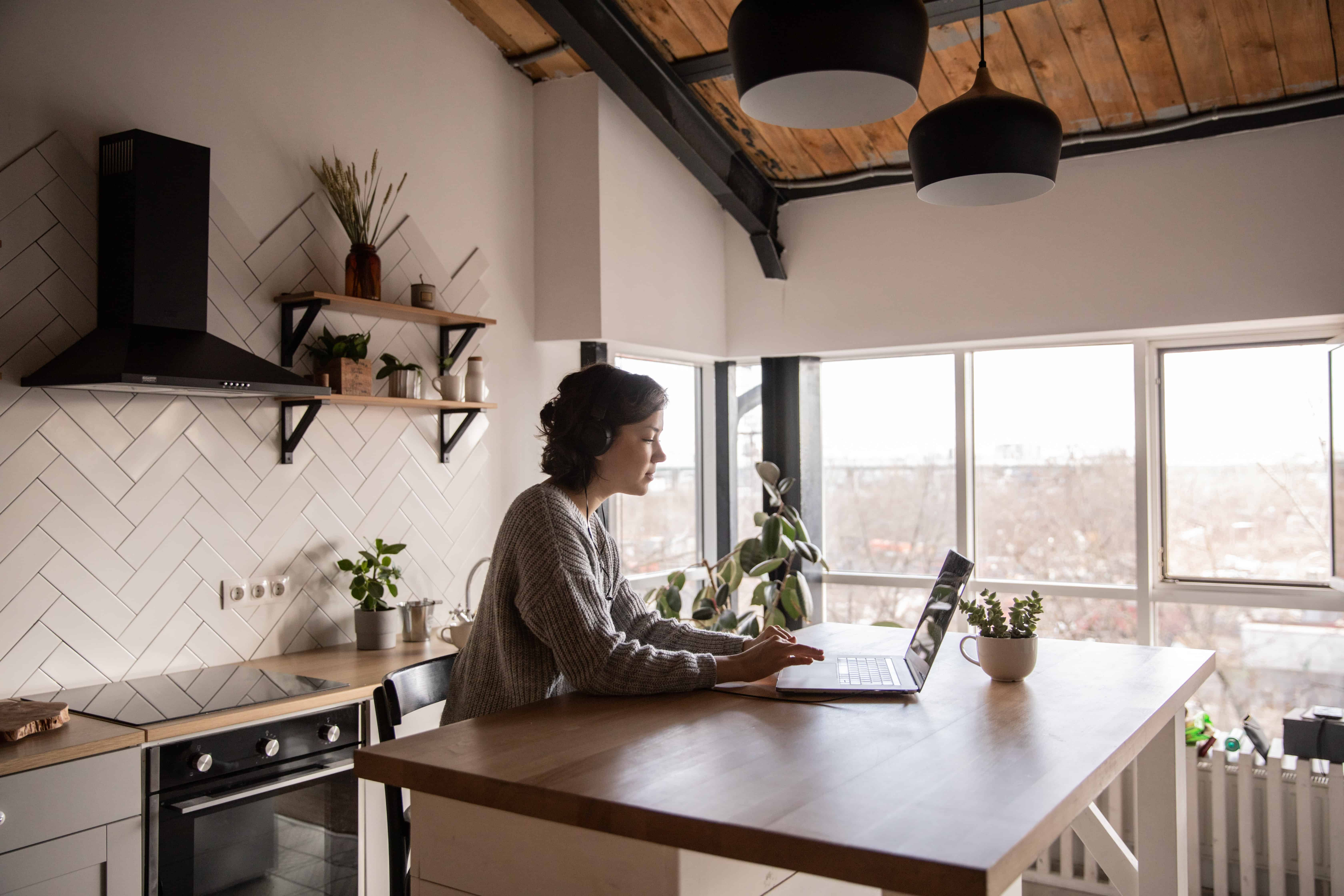 A woman working on her laptop in a kitchen.