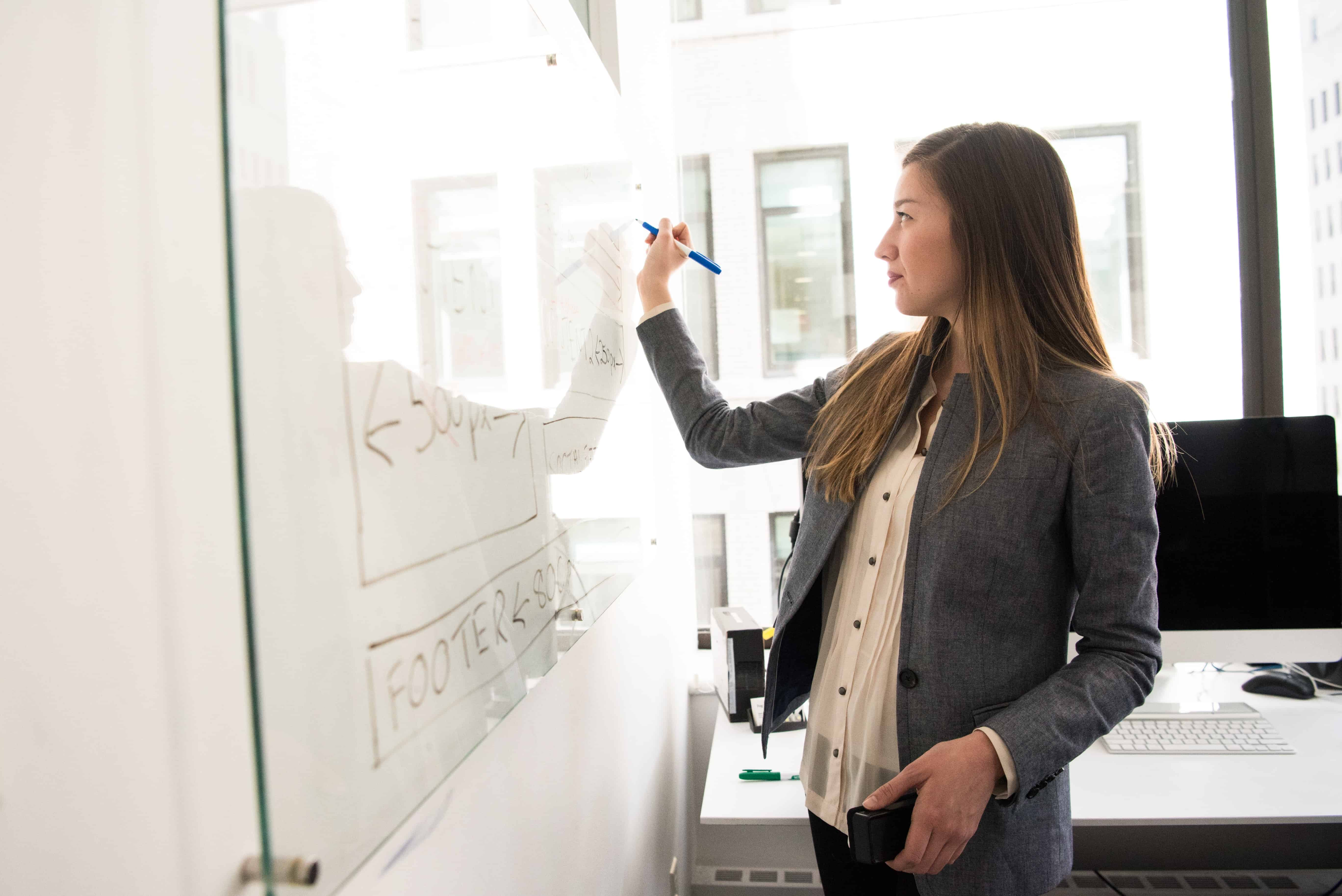 A woman writing on a whiteboard and motivating her employees.